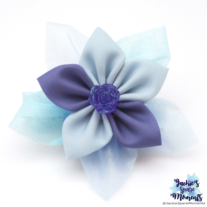 A flower made with different shades of blue and lilac organza and satin.