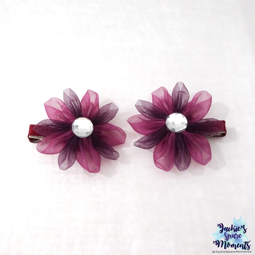 A pair of flower hair bows in autumnal eggplant hues.