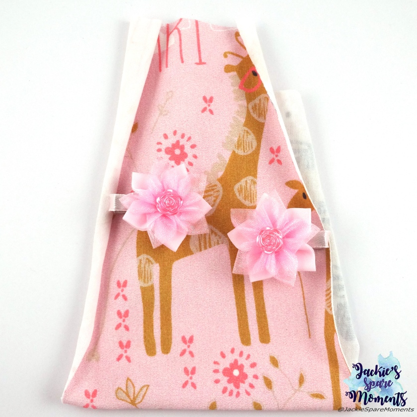 Small pink flower hair bows with flower centre flatback on the fabric off the dress